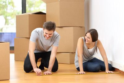 50532987 - happy couple moving house and taking measure together for the furnitures